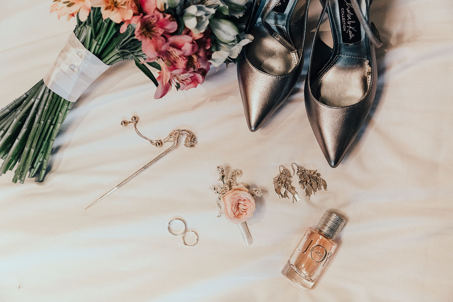 Wedding details layout made by photographer in Amsterdam shows bridal shoes, flower bouquet, rings, buttonhole and perfume.