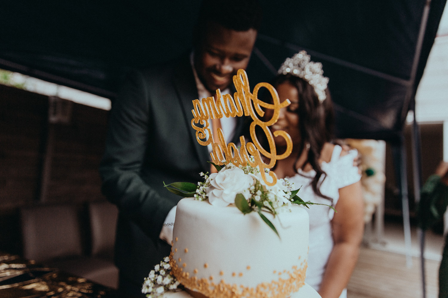 Picture made by wedding photographer in Amsterdam that shows wedding cake with couple names on the top. Married couple is out of focus is staying behind a cake and going to cut it.