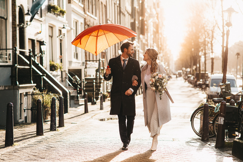 Cặp đôi nam nữ đang đi dạo với chiếc ô đỏ trong khi nhiếp ảnh gia đám cưới ở Amsterdam đang chụp ảnh