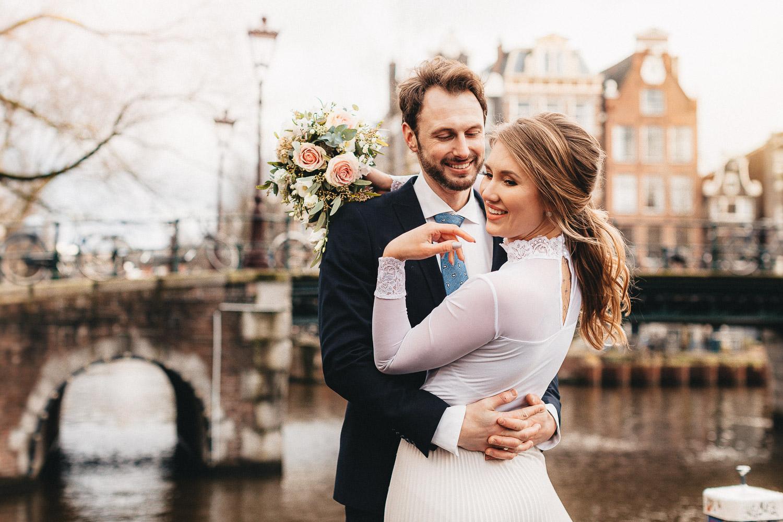 Cô dâu mỉm cười nhìn lại trong khi chú rể đang ôm eo cô. Cặp đôi đứng trước cây cầu ở thành phố Amsterdam cổ kính và chụp ảnh cưới ở Amsterdam