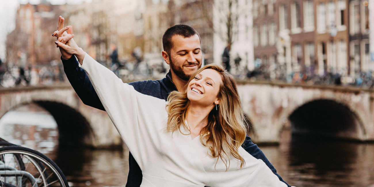 A happy beautiful couple is holding hands wide during a photoshoot for a wedding photographer in Amsterdam. They are staying in front of canal bridge in Amsterdam and smiling.