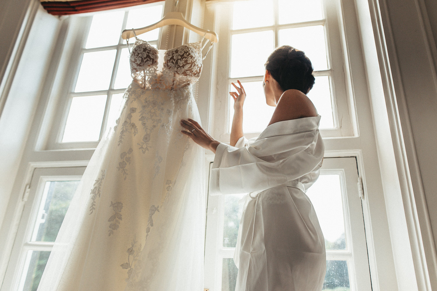 The bride is looking to the window and touching the dress while photographer makes a photo for wedding photography in Netherlands