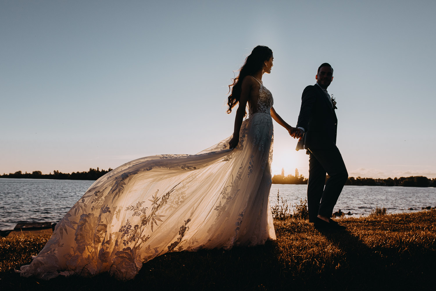 A bride in a long tail wedding dress holding a hand of a groom. They walking on the costline in Netherlands during the sunset time. Couple is posing for photographer in Amsterdam.