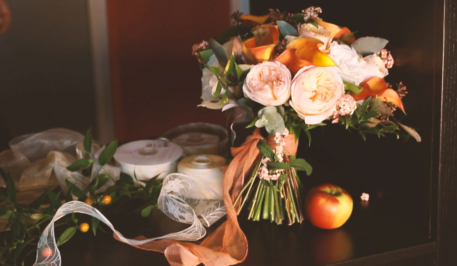autumn colours bridal bouquet is on the table with apple and laces.