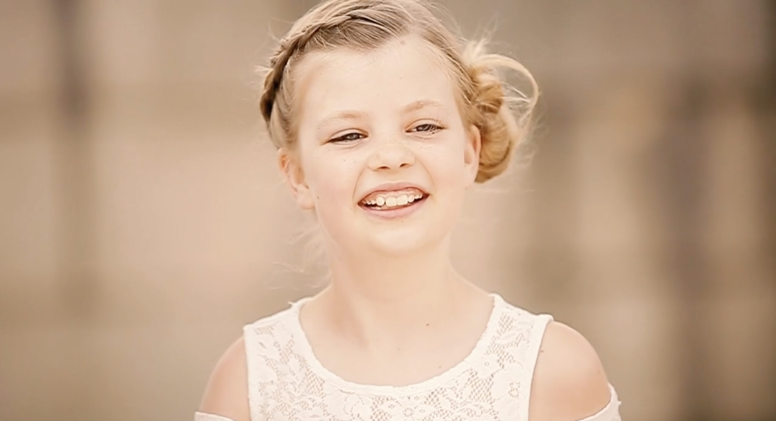 portrait of young blond girl in white dress captured by videograaf in Nederland