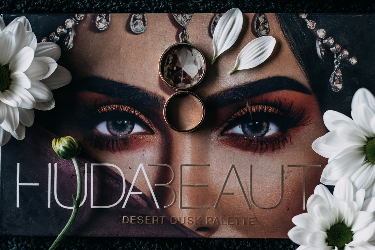 engagement rings lay down on make up palette with flowers, photo of details from Indian wedding in Netherlands