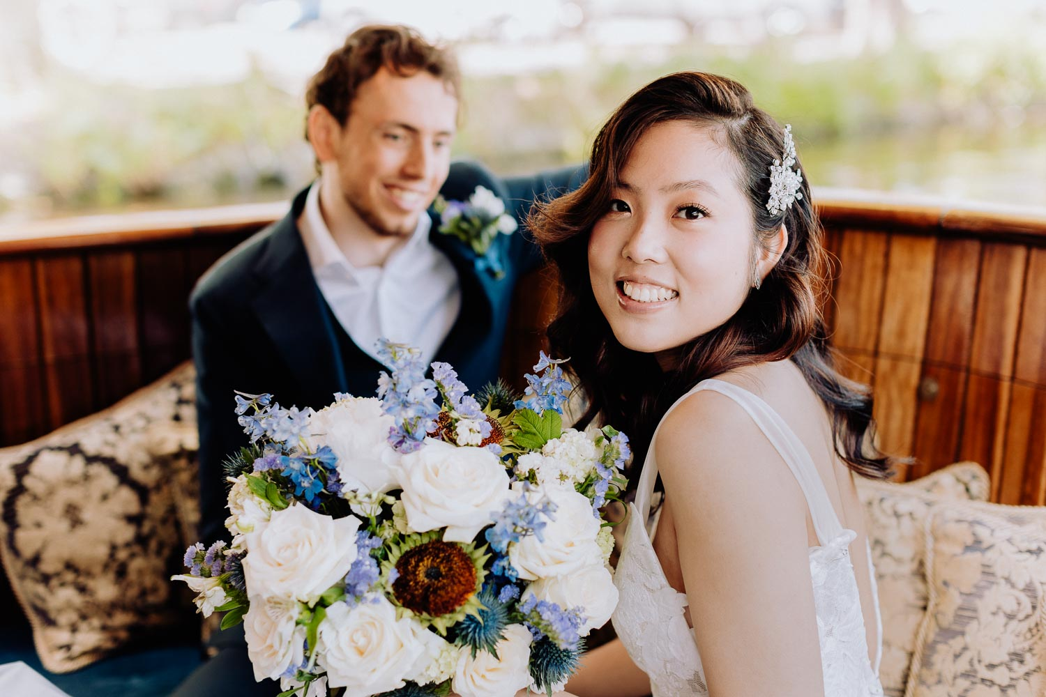 a beautiful bride sits on a chair and holds a bouquet of white roses in her hands, and the groom looks at her